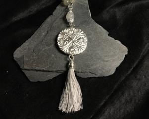 Silberamulett mit grauer Quaste